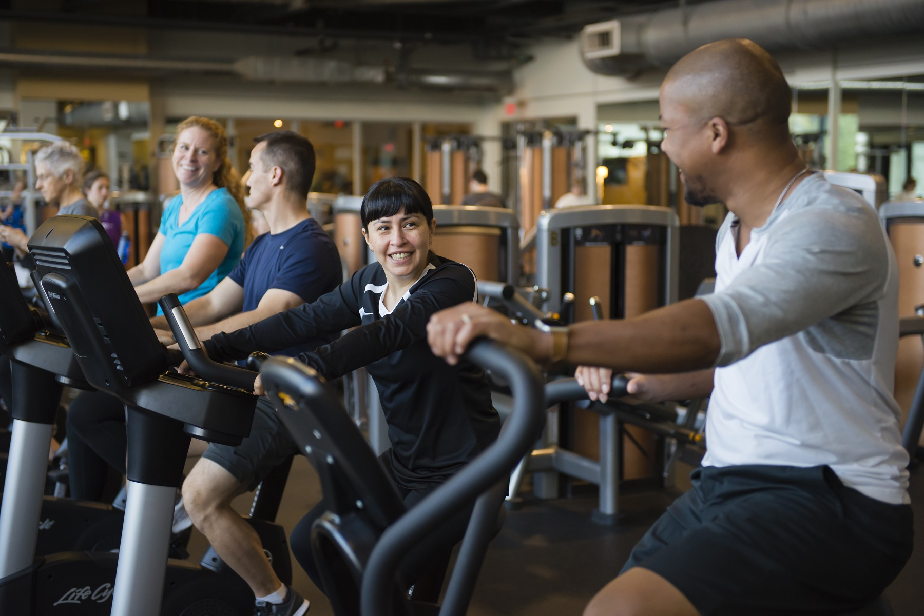 Row of 4 members on stationary bikes on march wellness & fitness center's fitness floor.