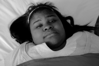 Still frame of a video from Sproutflix that includes a young woman lying in bed looking worried