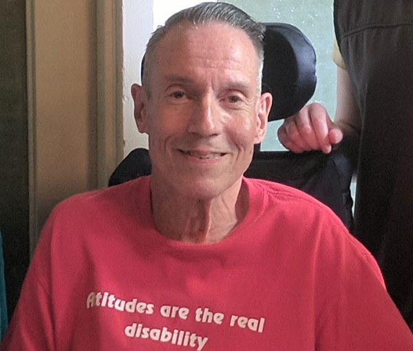 Jerry in a red shirt that says attitudes are the real disability