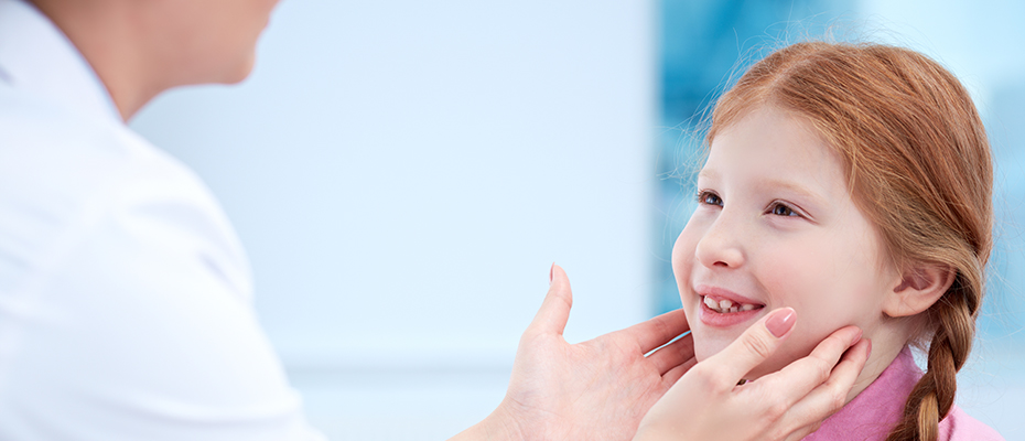A doctor inspects a child's throat for thyroid issues.
