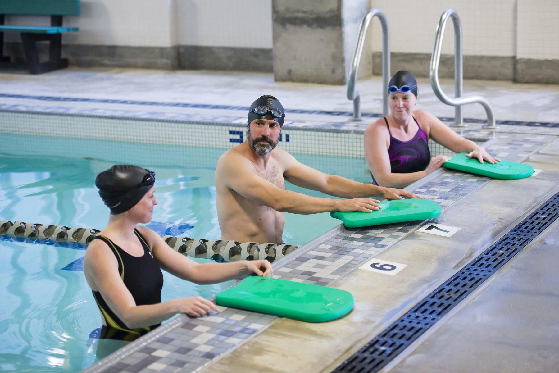 Three swimmers with kickboards resting at the wall in the lap pool.