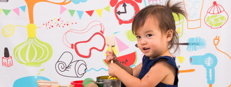 Toddler playing with a toy kitchen set, with a bright colorful mural in the background