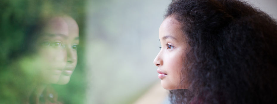A young girl, seen in profile, peering out a window. We can see a double reflection of her in the glass, and a blur of greenery outdoors beyond.