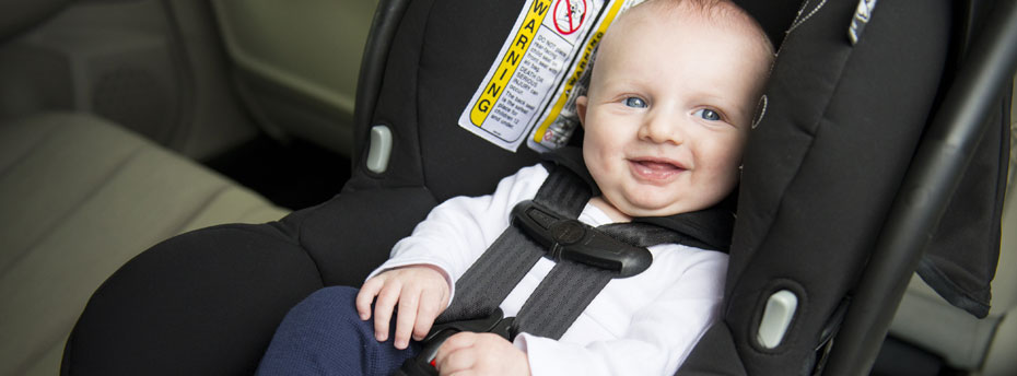 Baby fastened into a car seat designed for babies, well-padded with straps.