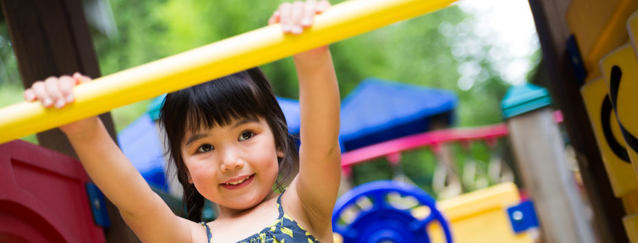 Smiling little girl grasping a yellow bar that's part of an outdoor playground set