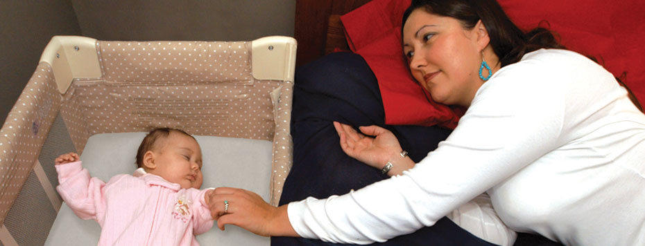Mother lying down on bed adjacent to baby in crib