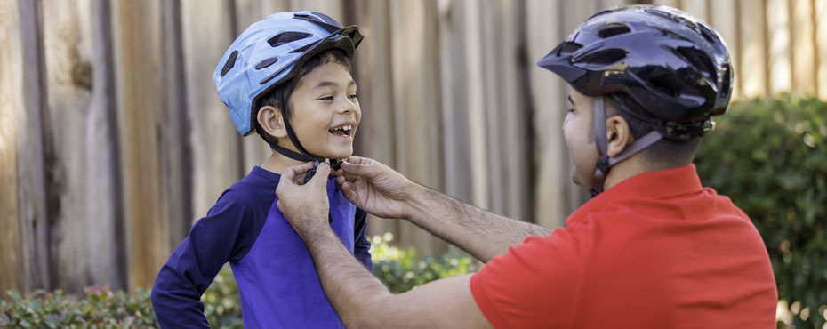 A father helps buckle the bike helmet for his son who is smiling