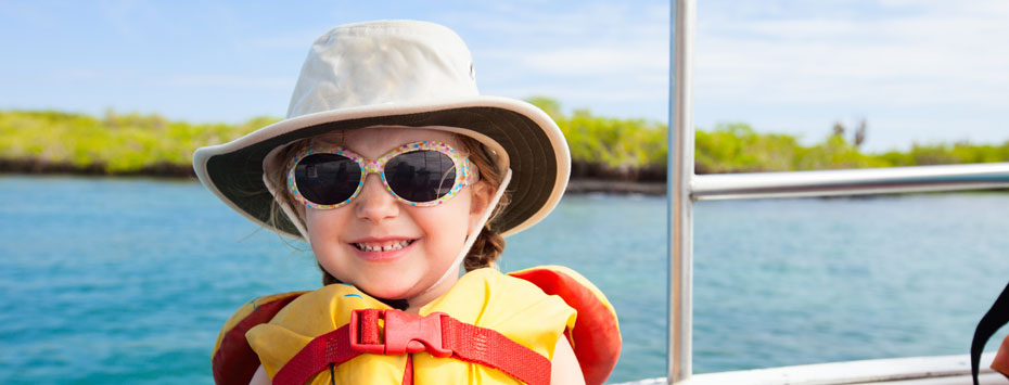 Toddler wearing sunglasses, sun hat, and personal floatation device