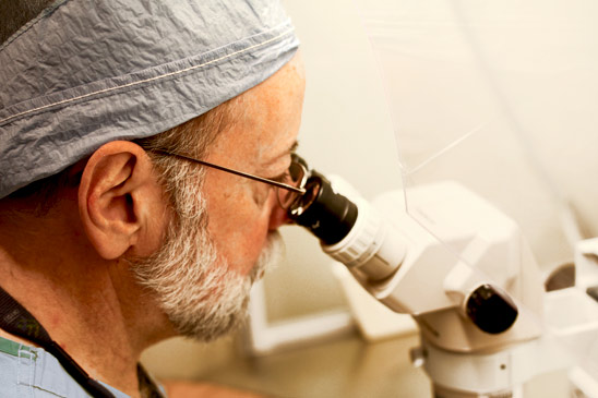 A doctor examines a specimen through a microscope in the fertility lab