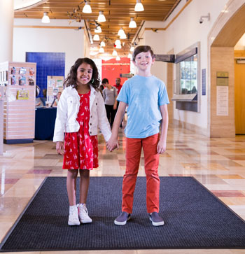 A young girl and boy holding hands and smiling in the center of a large lobby area