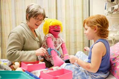 Child life therapist and Doernbecher patient playing with a doll