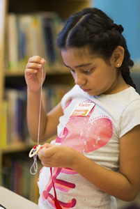 A female student working with yarn in the Hospital school program