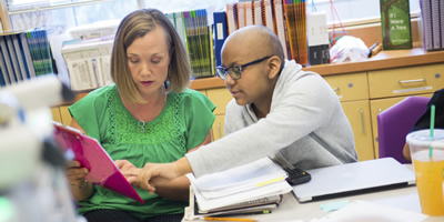 A teacher working with a student.