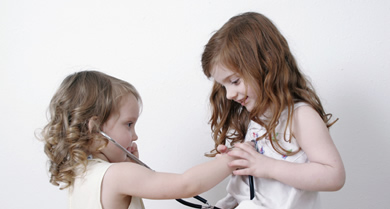 Two young girls pretending to be doctor and patient