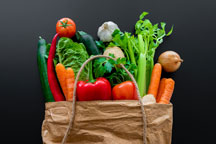 A grocery bag of colorful, healthy produce