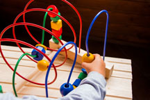 Child playing with a toy made of colorful wooden beads on looping wires