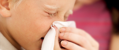 Child blowing nose into tissue