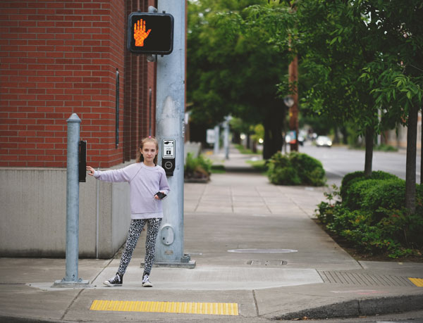 Girl waiting for the signal to change at a crosswalk.