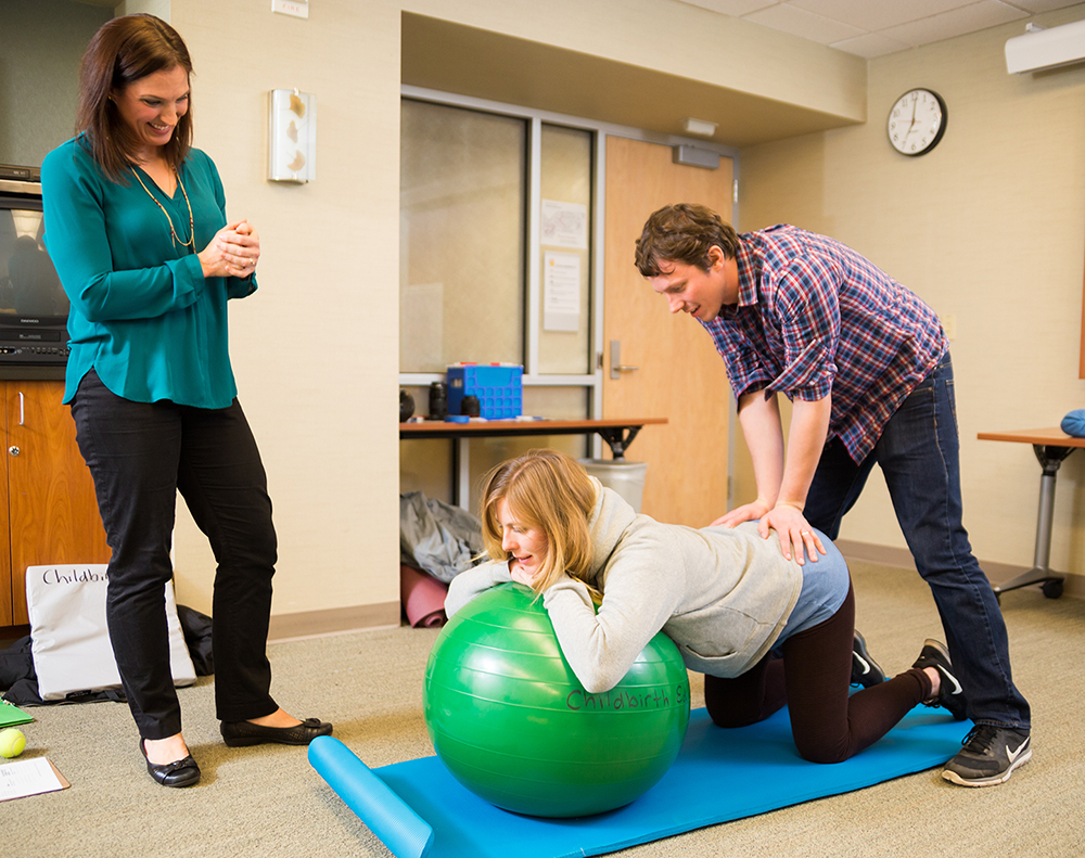 Expectant parents participate in stretching exercises at OHSU Childbirth and Early Parenting Classes as a provider looks on