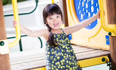 A young girl smiles and plays on a jungle gym structure