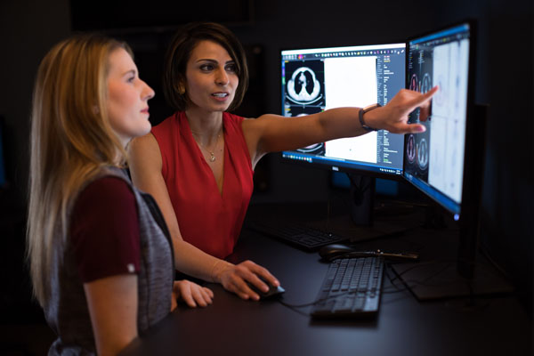 Nuclear Medicine Physician, Nadine Mallak discussing images on a PACS monitor with a colleague.