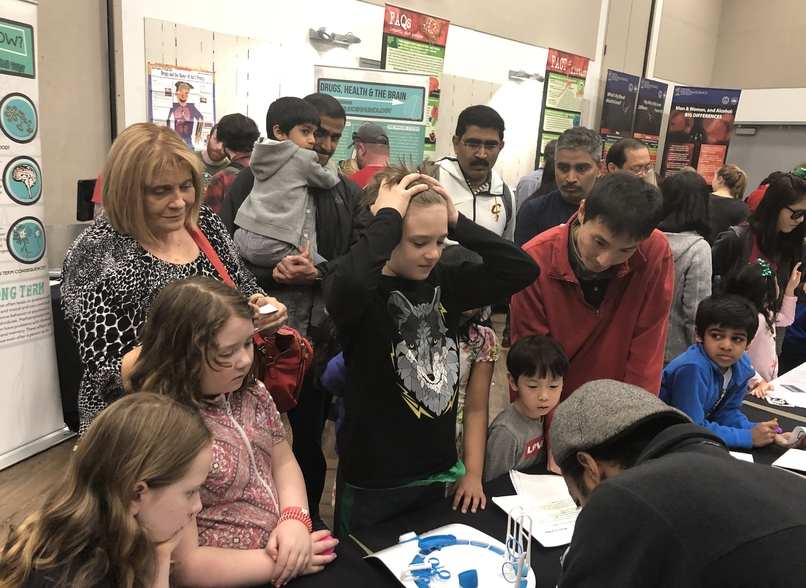 A group of young people watch a neuroscience display.