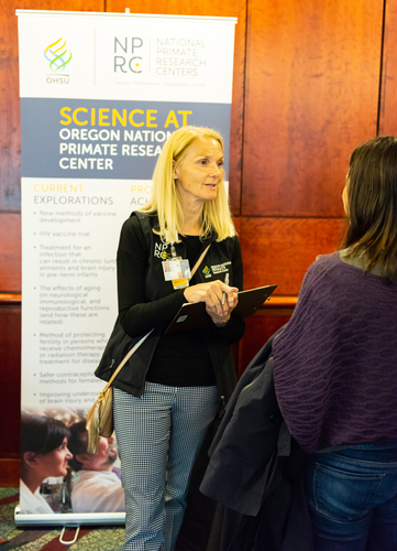 A representative from the Oregon National Primate Research Center speaks to a lecture patron.