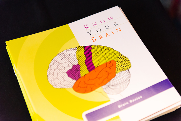 "A pamphlet from NIH called ""Know Your Brain"" displayed on a table."