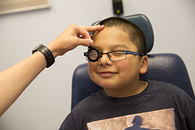 Boy with glasses having his eyes examined for glaucoma.