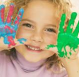 photograph of a child holding their hands up next to their face, the hands are covered in colorful fingerpaint
