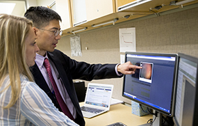 Dr. Chiang reviews images of the eye sent from another hospital to diagnose retinopathy of prematurity in infants.