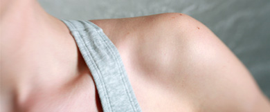 A closeup of the shoulder of a person wearing a tank top.