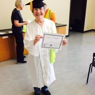 A graduate of the Matter of Balance program displaying their certificate while wearing a cap and gown.