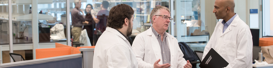 Brett Johnson, Ph.D., (left) Gordon Mills, M.D., Ph.D., and Joshi Alumkal, M.D., in one of the shared laboratory areas within the Knight Cancer Research Building.