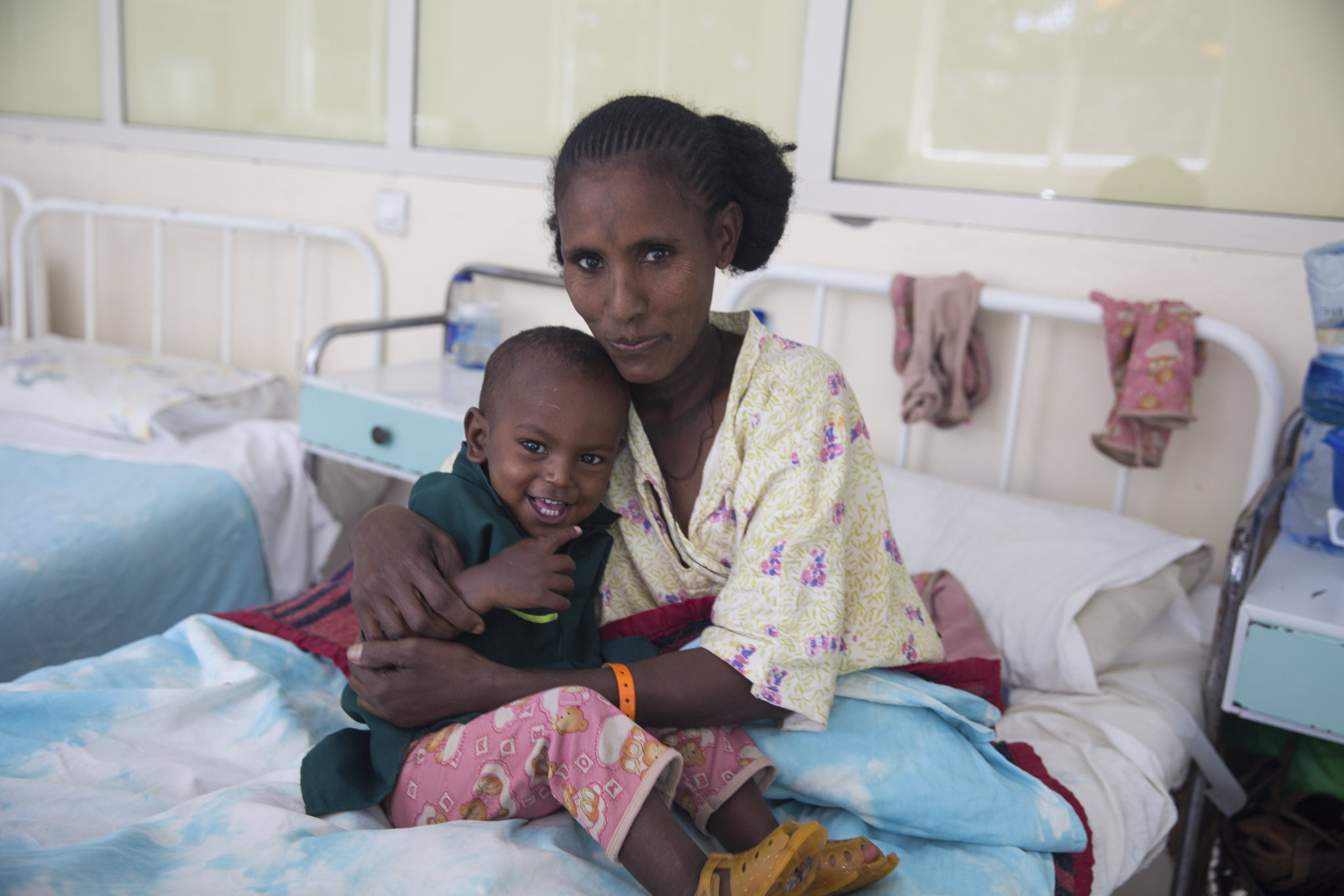 A mother and her young son sitting in a patient care bed smiling