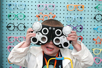 A child plays with eye exam equipment.