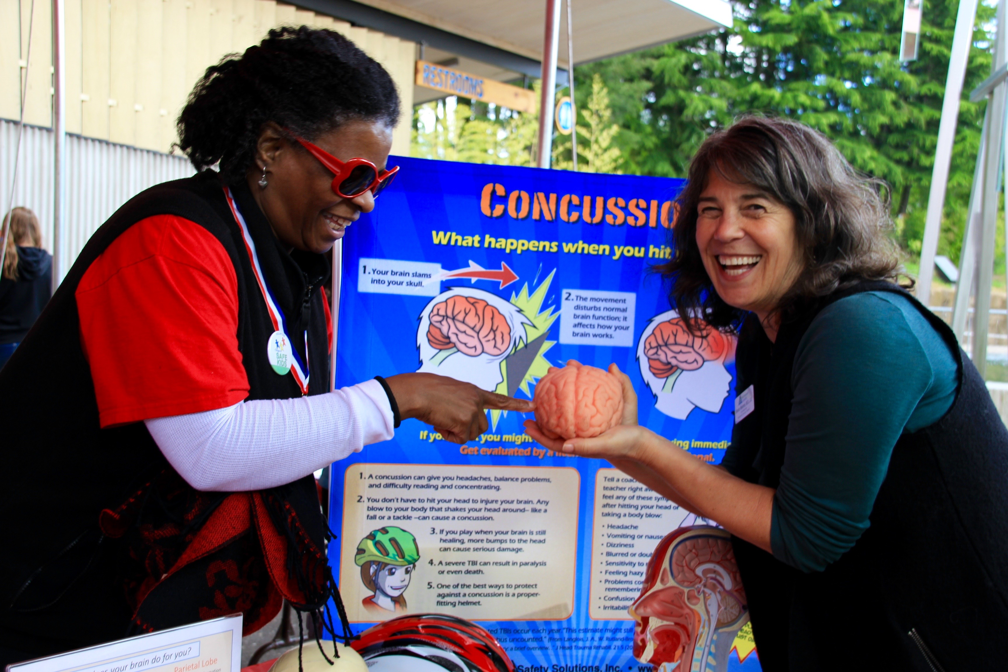 Two ThinkFirst volunteers holding a model brain as part of a concussion information display.