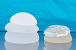 An image showing silicone and saline breast implants in different sizes