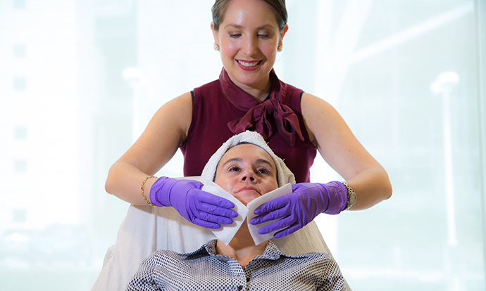Aesthetician Andrea Fontana with a client doing a facial.