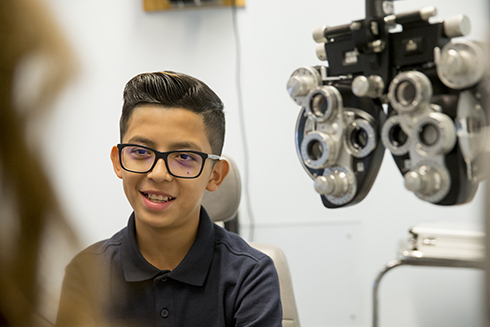 Teen boy with glasses has his eyes examined at Casey Eye Institute