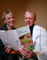 A women's health doctor shows a patient a publication of patient care information