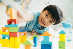A young boy plays with building toys