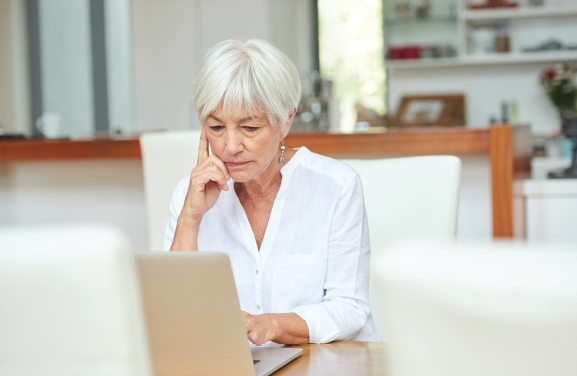 woman sits at computer looking thoughtful