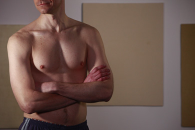 A man showing off his hairless chest.
