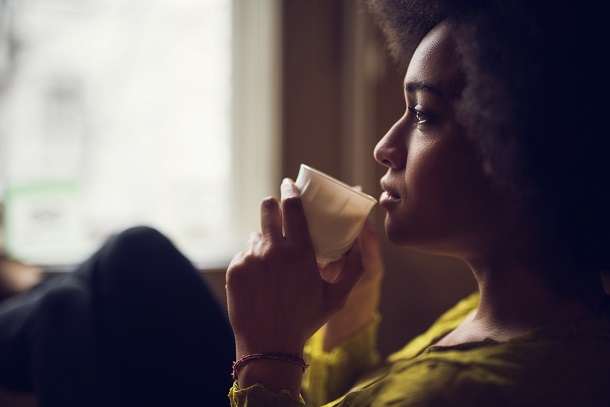 woman sits in front of screen sipping a drink