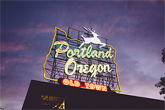 The iconic Oregon-shaped white stag sign at dusk. Text: Portland Oregon Old Town