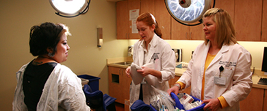 Two women's Health nurses prepare to examine a patient