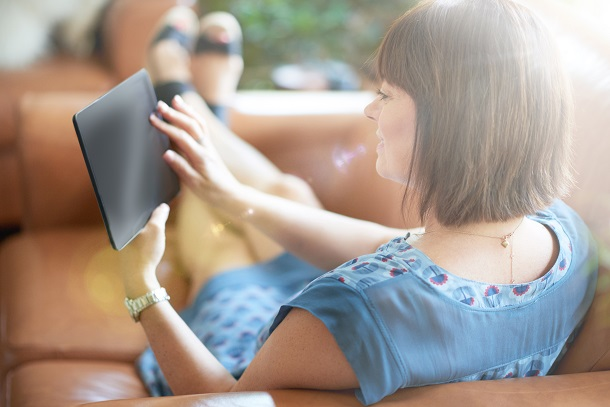 A woman relaxes on the couch while reading a digital tablet