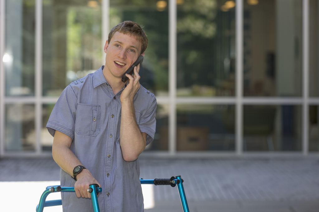 young man with a walker on the phone