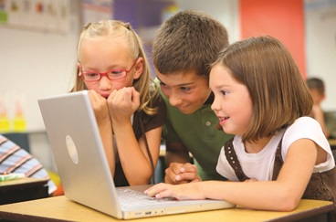 3 Children Looking at a laptop in a classroom